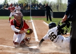Oklahoma catcher Jessica Shults is unable to put out Jenna Marston, (26) who slides safely into home in the second inning, giving the Tigers the 1-0 lead. Watching from first base is Catherine Lee (23)