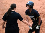 Rhea Taylor celebrates with the first base coach after singling off Oklahoma pitcher Keilani Ricketts. (Photo by Nick Gerhardt)