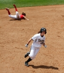Kathryn Poet heads to third base as the Illinois State shortstop dives for an infield grounder.