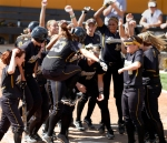 Teammates gather around home plate as Catherine Lee (23) jumps up preparing to score.