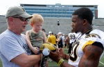 Sophomore tailback Henry Josey signs a football for four-year-old Jonas Waldschlager, who is being held by his grandfather John. John and his wife are season ticket holders and this was Jonas' first time on the field meeting the players.
