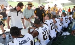 Fans file past Mizzou football players, having everything from posters to footballs to helmets and photographs signed by the players.