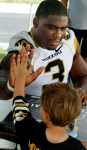 Jacquies Smith gets a high five from a fan during Fan Day Sunday. Smith is one of the team's four captains.