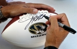 Coach Gary Pinkel signs a football for a fan.