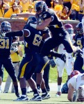 Members of the defensive line celebrate a turnover during the Homecoming game against Iowa State.