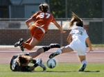 Missouri's Brooke Williams (3) and Texas players Julie Arnold (37) and goalkeeper Alexa Gaul go flying on a play near the Texas goal. Missouri lost the game 2-1.