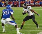 Kendial Lawrence (4) tries to run past Kansas Anthony Davis (30). Lawrence rushed the ball 17 times for 63 yards and a touchdown.
