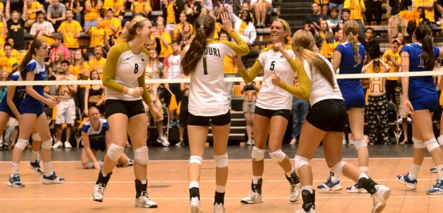 Teammates Whitney Little (8), Molly Kreklow (1), and Sarah Meister (4) celebrate a Lisa Henning (5) kill. Henning had a career high 27 kills in the match. Dec. 15, 2011 file photo.