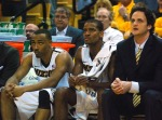 Kim English (center) gets benched after recording his third personal foul in the first half, a technical foul for aggressively slamming the basketball to the floor. English is shown here between forward Matt Pressey (left) and Missouri's Director of Athletic Performance Todor Pandov (right).