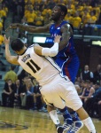 Jayhawks guard Elijah Johnson runs over Michael Dixon in the first half.