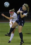 Lauren Flynn (11) kicks the ball to a teammate around Illinois defender Niki Read (5).