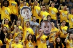 Students cheer, holding posters of Phil Pressey, left, and Keion Bell in the student section.