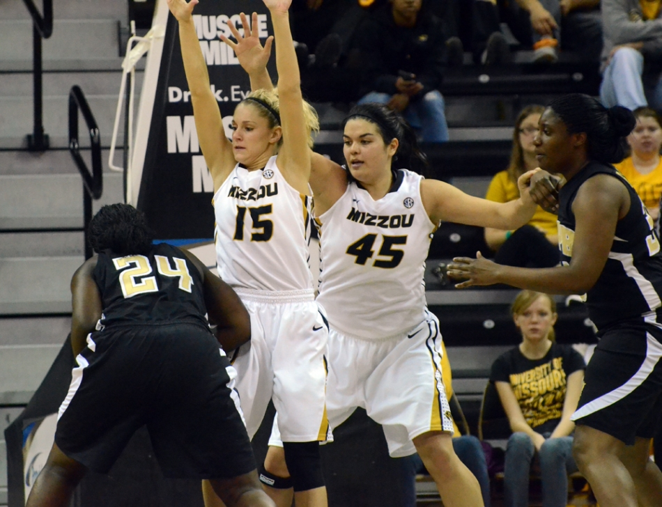 Sophomore guard Kyley Simmons (15) jumps to block Golden Lion Marion Thompson (24) from the net as Liz Smith watches. Simmons scored one 3-pointer for the Tigers, but made a team-high six assists.