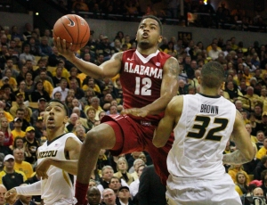 Alabama's Trevor Releford drives to the basket between Phil Pressey (1) and Jabari Brown (32).