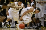 Dai-Jon Parker, left, Jabari Brown (32) and Phil Pressey (1) scramble for the loose ball in the first half.