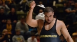 Missouri heavyweight Dom Bradley rips off his headgear before lifting up both hands in celebration. Bradley beat Keldrick Hall of Oklahoma 10-4 to remain undefeated. Bradley ranks as the top heavyweight in the nation after taking an olympic redshirt last season.