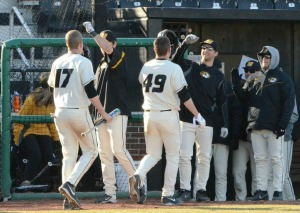 Josh Lester (17) and Scott Sommerfeld (49) receive greetings in the Missouri dugout after scoring in the fifth inning of Wednesday's game.
