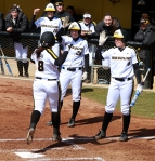 After hitting a home run, Nicole Hudson (8) is greeted at the plate by Jenn Marston (26) and Mackenzie Sykes (4).