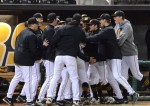 Missouri starting pitcher Rob Zastryzny is mobbed by teammates as he approaches the Missouri dugout after completing his eighth inning of work against San Francisco on Friday night.