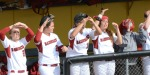 Arkansas players celebrate the success of their rally caps in the dugout.