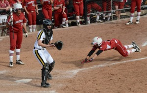 Arkansas' Clarisa Navarro (11) slides into home to score the game-winning run on pitcher Nicole Hudson's wild pitch.  The Razorbacks won 11-10 in eight innings.