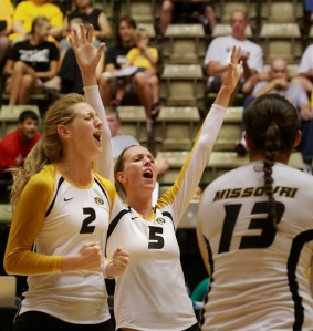 Emily Thater (2), Lisa Henning (5) and Emily Watson (13) celebrate a kill in the first game of the Tiger Invitational volley tournament Friday, Aug. 30, 2013 at the Hearnes Center in Columbia, Mo.