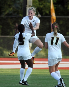 Reagan Russell (6) jumps up to celebrate her goal with teammate Brittany Conley (5) as Lauren Flynn (11) watches. Photo by Karen Mitchell