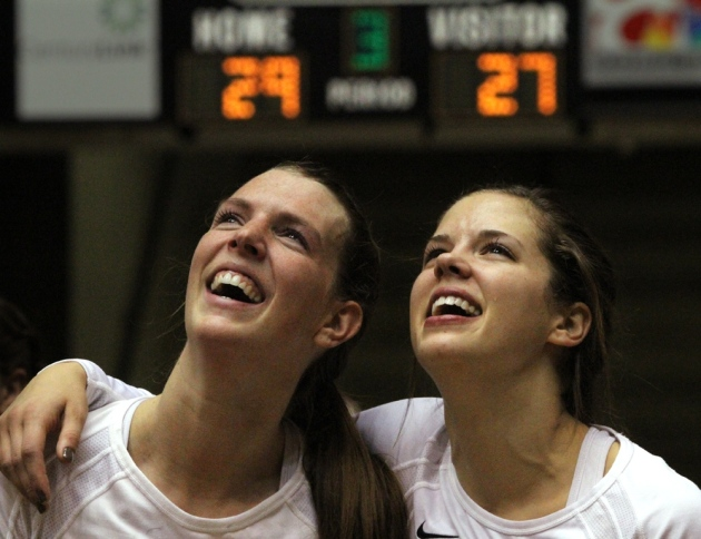 Seniors Lisa Henning, left, and Molly Kreklow watch a video of their career highlights after Wednesday's game. The score on the board is from the third match against Arkansas.
