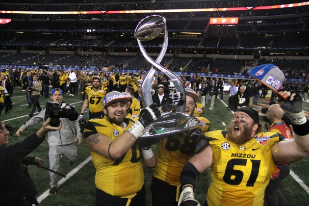 Anthony Gatti (70), Justin Britt (68) and Max Copeland (61) celebrate on the field with the Cotton Bowl trophy after the game.