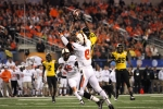 Bud Sasser (21) goes up for the pass, tightly guarded by an Oklahoma State defender.