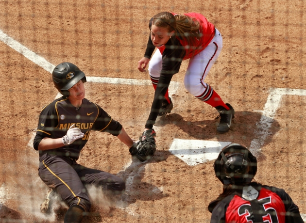 Sami Fagan grimaces as she is tagged out sliding into home by pitcher Chelsea Wilkinson as catcher Katie Browne watches.