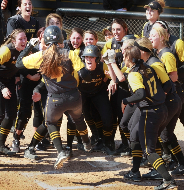 Mackenzie Sykes jumps onto home plate  and into the crowd of cheering teammates after hitting a walk-off home run Saturday, winning the game 6-3.