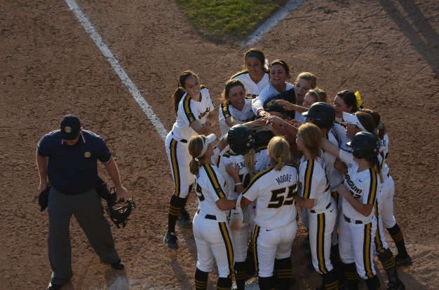 The Missouri softball team greets Natalie Fleming at home plate after her walk-off home run at University Field in Columbia, Mo. on Friday, April 18.