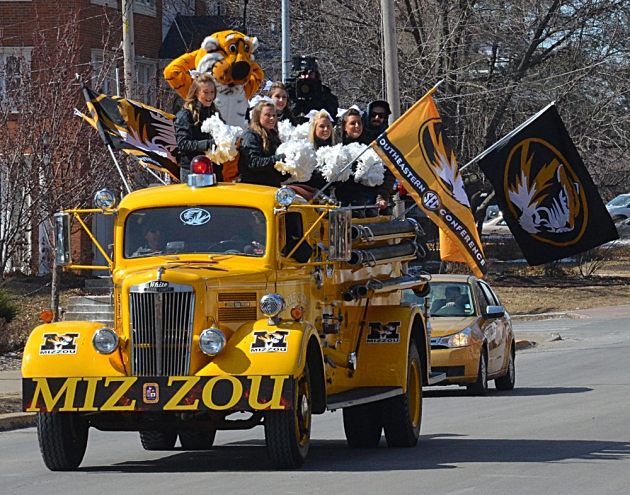 A fire truck carrying Missouri cheerleaders, Truman the Tiger and a videographer rolls down Rollins Street in front of Tiger Plaza on March 4, 2014, to take part in the filming of a commercial for the upstart SEC Network. The network is scheduled to launch in August. Photo by Philip Joens.