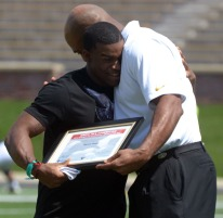 Former MU running back Henry Josey embraces assistant athletic director Pat Ivey on Saturday, April 19, 2014 at Memorial Stadium in Columbia, Mo. Josey was presented with an award for being named a National Strength and Conditioning Association All-American.
