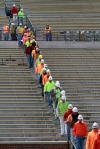 Workers file onto Faurot Field from the east side stands Friday. They were treated to a barbeque lunch and signed the last beam of the construction site.