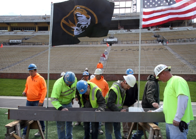Workers sign a steel beam marking the end of a major phase in construction at Memorial Stadium on Friday. The new seating and concession facilities should be finished in time for the first home game.