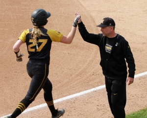 Mack is congratulated by coach Ehren Earleywine as she rounds third base.