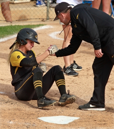 Corrin Genovese is helped up by coach Ehren Earleywine after was was put out at home in the fifth inning.