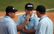 Umpires John Baca, left, Andy Trent, center and Royce Eller discuss one of several contested plays in the game.