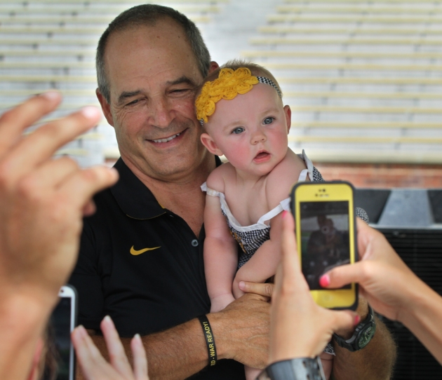 MU football coach Gary Pinkel holds 8-month-old Bristol Kennedy at the annual Fan Day event on Sunday, Aug. 10, 2014, at Memorial Stadium. Bristol is the daughter of Robert and Secley Kennedy of Columbia. Photo by Karen Mitchell