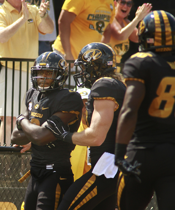 Darius White, left, strikes a pose after scoring a touchdown.