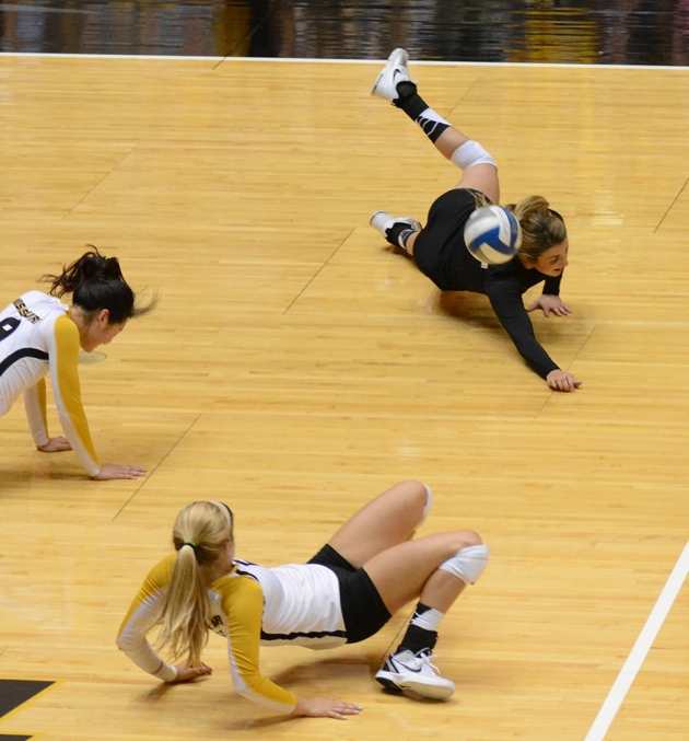Libero Sarah Meister, in black, and two of her teammates are unable to reach the ball. The team committed numerous errors, including 26 attack errors and 11 reception errors.