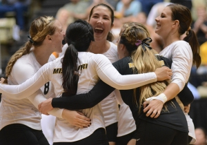 The team hugs each other as they celebrate a won point in the third set.
