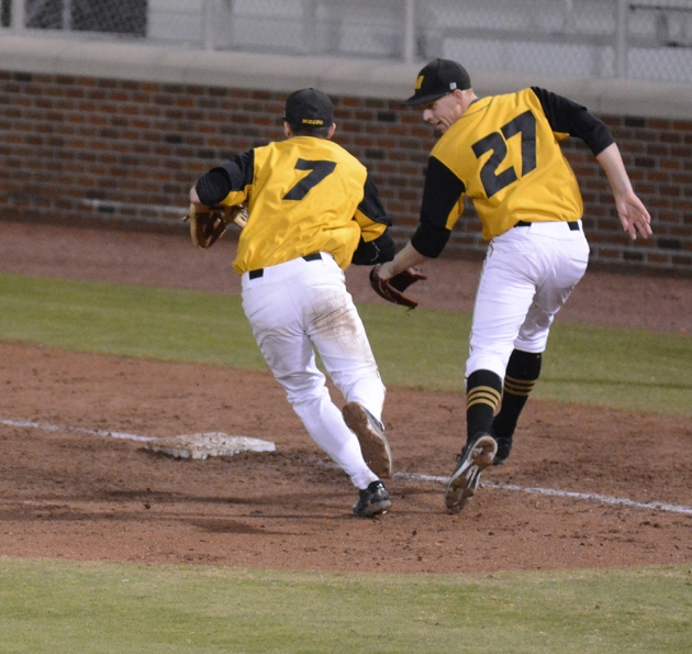 First baseman Logan Bone (7) and pitcher Nolan Gromacki converge on a groundball at first base. Logan would end up fielding the ball cleanly and making the out.