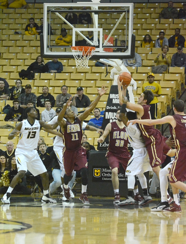 Missouri's Keith Shamburger (14, hidden) draws a key foul on Elon's Tony Sabato (15, hidden) as Missouri's Montaque Gill-Caesar (13) and Johnathan Williams III (3 in white, hidden) and Elon's Kevin Blake (11), Ryan Winters (32) and Tanner Samson (3 in red, hidden) look on.