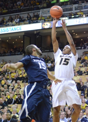 Wes Clark (15) shoots a three in the corner over Xavier's Myles Davis (15) on Saturday, Dec. 13, 2014. Clark didn't have much impact offensively, as he scored three points off the bench for the Tigers.